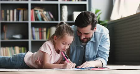pai : Loving young adult dad help cute small daughter draw together, happy father teach kid preschooler enjoy family weekend creative hobby art activity lying on warm floor carpet talk color picture at home