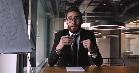 тренер : Motivated successful young arabic businessman in eyeglasses sitting at office desk, looking at camera. Smiling pleasant middle eastern ethnicity male speaker coach trainer recording educational video.