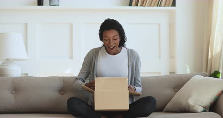 etnia africano : Curious millennial mixed race girl sitting on sofa, unpacking cardboard parcel, surprised by fast delivery service. Interested young african american woman unboxing purchase from internet store.