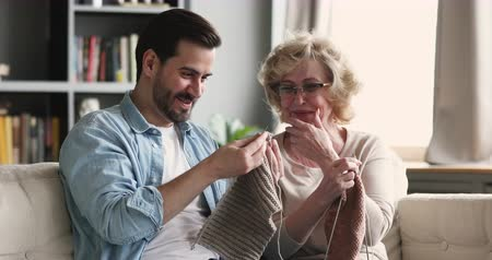 ago : Funny happy young adult grown son helping senior older mother teaching knitting laughing together, smiling 2 two generations family enjoy leisure handwork hobby relax having fun sit on sofa at home Filmati Stock