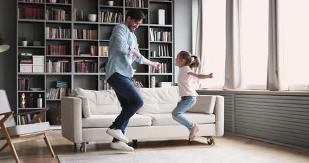 taniec : Active cheerful young adult dad dancing having fun with small kid daughter imitate father moves at home, happy parent daddy and cute little child girl jump play together enjoy funny activity indoors