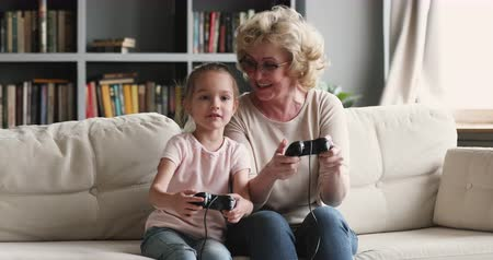 konzol : Funny excited two generations family gamers play video game at home, happy old grandmother and cute child girl granddaughter hold joysticks controllers win videogame hug celebrate victory sit on sofa Stock mozgókép