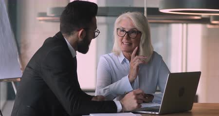 stary : Pleasant mature female financial analyst consulting young arabian businessman in suit, sitting at desk. Happy mixed race younger and older business people discussing project ideas, using laptop.