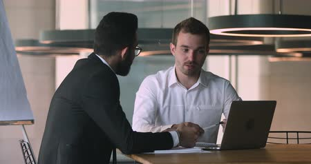 ringraziare : Confident caucasian male financial advisor bank worker broker explaining deal benefits, showing presentation on computer to focused arabic businessman, shaking hands after making agreement in office.