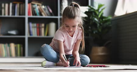 koncentracja : Cute concentrated little kid girl draw color pencil play alone on floor, pretty preschool child coloring picture at home enjoy creative activity relax sit on carpet, children playtime education concept Wideo