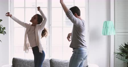 casal : Happy joyful young adult couple in love dancing in living room together, active carefree millennial husband and wife home owners having fun enjoying funny party in new modern apartment, freedom concept