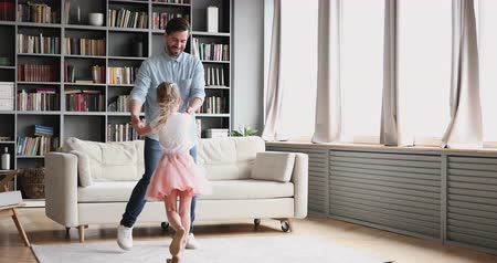 przedszkolak : Affectionate loving young adult dad teaching dancing with cute small child daughter princess wear crown skirt having fun in modern living room playing ball together enjoy sweet funny activity at home. Wideo