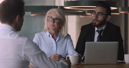 recrutamento : Confident middle aged female company boss leader with young arabian hr manager sitting at desk, holding job interview meeting with caucasian male candidate, asking questions, listening to answers.