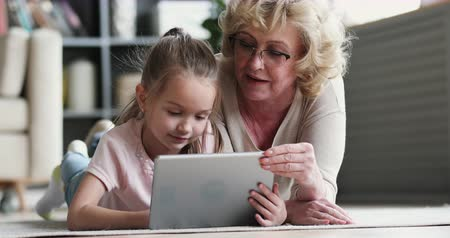 przedszkolak : Old mature grandma nanny teaching cute small preschool granddaughter learning reading ebook on digital tablet, two generation family grandparent and grandchild using pad device tech on floor at home Wideo