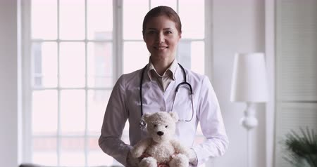 ветеринарный : Smiling young female doctor wear white medical coat hold teddy bear toy look at camera, happy professional medic nurse pediatrician portrait, children healthcare paediatric services specialist concept