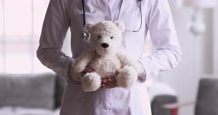 плюшевый мишка : Woman paediatrician wear white uniform holding teddy bear as pediatrics and children healthcare concept, female professional medic nurse pediatrician with fluffy toy in hands close up view