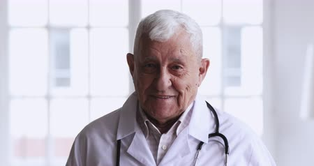 generale : Smiling kind professional old senior male doctor wear white coat stethoscope looking at camera, happy gray-haired elder 80s man successful medic physician gp surgeon posing for close up face portrait Filmati Stock
