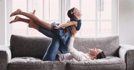 den matek : Happy young adult parent mum holding lifting cute kid daughter playing plane. Active mom teaching yoga exercise having fun with child girl flying up. Family enjoy leisure airplane game relaxing on sofa Dostupné videozáznamy