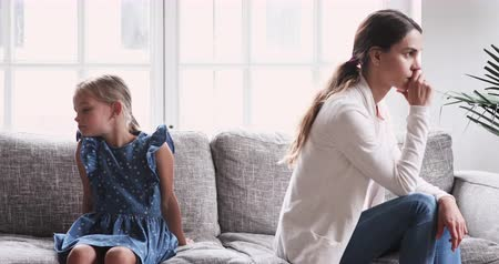 аргумент : Unhappy mother and small daughter sit on sofa avoid talk. Worried mom ignore upset kid turn back think of family fights. Young parent feel guilt about child psychological trauma after conflict concept