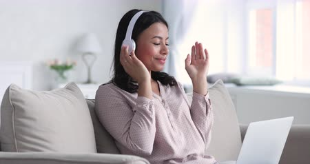 melodi : Smiling young african american woman wear wireless headphones using laptop computer lounge sit on sofa, happy relaxed mixed race lady enjoying listening music while surfing internet resting at home