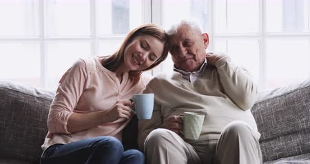 внучка : Happy senior elder father grandfather and young adult granddaughter grown daughter talking bonding drink tea sit on sofa, loving 2 two generations family embracing enjoy friendly conversation at home Стоковые видеозаписи