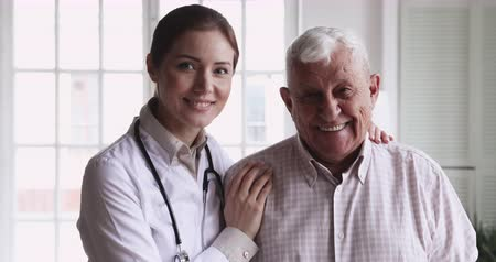 sağlamak : Smiling young female doctor physician wear white coat stethoscope embrace happy senior elder patient look at camera in hospital, eldercare, old people healthcare medic service concept, close up portrait Stok Video