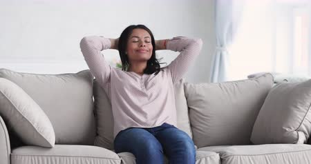 respiração : Serene relaxed healthy young african woman lounge on comfortable sofa holding hands behind head eyes closed, calm single mixed race lady breath fresh air feel no stress concept rest on couch at home
