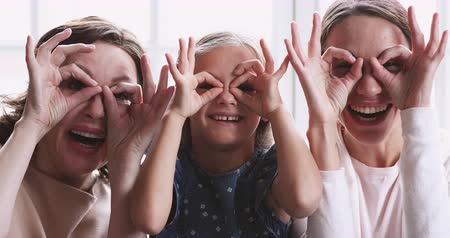 três pessoas : Cheerful intergenerational family make funny faces glasses laugh look at camera. Cute small girl granddaughter, old grandma and young daughter mom having fun. Happy 3 generation women family portrait Vídeos