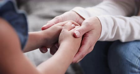den matek : Adult mother volunteer holding hands of kid girl close up view. Foster care parent protect small child daughter give hope love care support concept. Children patient health donation charity adoption