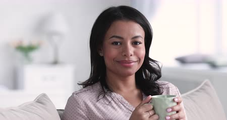 çay : Smiling relaxed young african american ethnic woman hold cup drink tea looking at camera laughing sit on sofa at home, happy adult mixed race lady dental smile enjoy well being, close up face portrait Stok Video