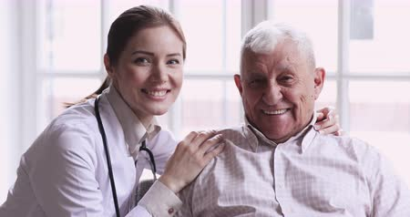 caregiver : Happy healthy senior grandpa patient and young female doctor look at camera provide medical aid service medicare, healthcare insurance for older people and geriatric elder care at nursing home concept