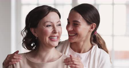 den matek : Joyful happy mid aged mature mommy and cheerful young adult daughter dental smiles embracing laughing looking at camera having fun. Two 2 age generations women enjoy good relationship. Family portrait