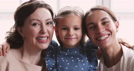 milující : Cute adorable small child granddaughter hug smiling older mature grandmother and loving mommy young adult daughter. 3 three age generations look at camera. Happy multigeneration women family portrait Dostupné videozáznamy