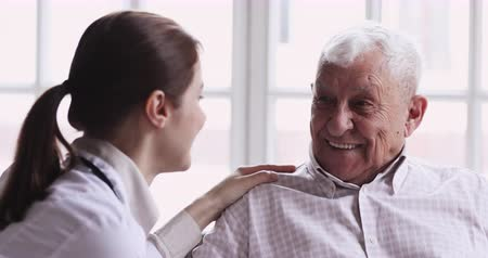 rada : Smiling healthy senior elderly grandpa talk to caring young female doctor physician examining aged patient in hospital during medical checkup visit, eldercare treatment, old people healthcare concept Wideo