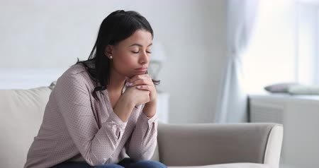jealous : Sad thoughtful young african american single woman pensive face looking away thinking of problems sit alone at home, upset mixed race ethnic lady feeling depressed reflecting feel lonely concept Stock Footage