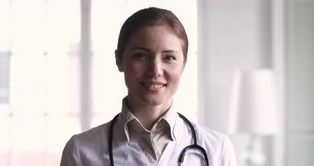 lab employee : Smiling confident young adult female doctor close up portrait, friendly happy woman physician or nurse professional general practitioner posing with stethoscope looking at camera in medical office