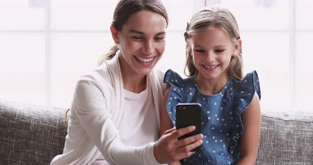 babysitter : Cheerful young adult mum show cute small kid daughter funny mobile video. Happy family mother and little preschool girl having fun use smartphone. Parent with child laugh looking at phone sit on sofa