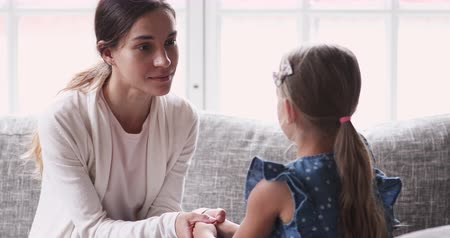 щит : Caring young mom holding hands talking to small child girl. Foster care parent comforting helping adopted kid give care and protection. Loving mum and small daughter having trust conversation at home