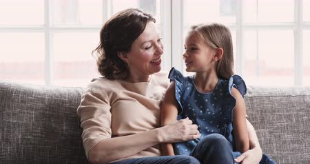 честный : Adorable cute preschool granddaughter talk to caring mature middle aged grandmother. Old babysitter listening small grandchild share secret. Two age generation enjoy trust conversation bonding at home