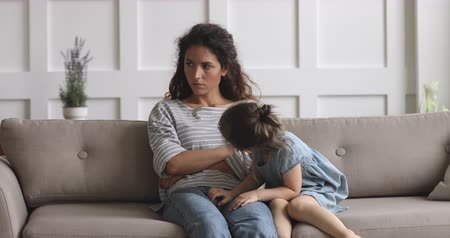 babysitter : Offended young mother crossed hands, ignoring small hyperactive daughter, sitting together on couch. Irritated by little kid nanny babysitter not talking after quarrel, children parents conflict. Stock Footage