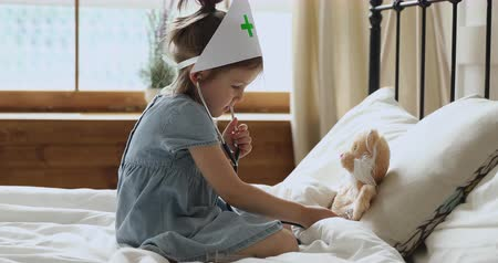kutyák : Small preschool cute kid girl wearing medical hat, pretending to be doctor. Little adorable child using stethoscope, playing as nurse or veterinarian with fluffy toy, treating soft dog in bedroom.