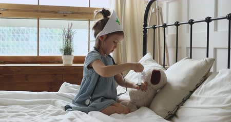 seringa : Adorable small child girl sitting on comfortable bed wearing nurse medical hat, pretending to be doctor, playing with favorite soft toy, making injection with disposable syringe, having fun alone at home.