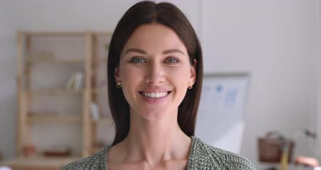 konsultant : Head shot close up happy young attractive confident businesswoman looking at camera. Excited pleasant female professional teacher trainer coach standing in modern workplace, showing positive emotions.