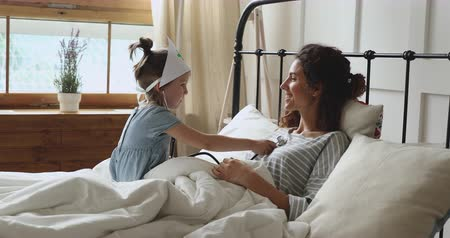longen : Concentrated playful little preschool kid child daughter wearing medical hat, using stethoscope, pretending to be a doctor nurse, listening smiling mommy breathing deeply, lying in bed at home.