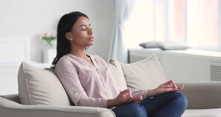дзен : Healthy mindful serene young african american lady meditate with eyes closed sit on sofa relaxing at home do yoga exercise breathing fresh air feel balance peace of mind no stress free in living room