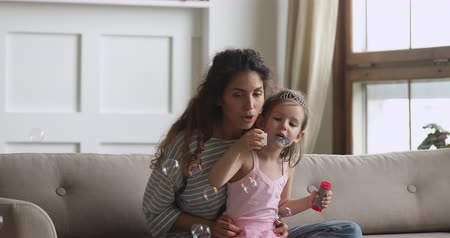 общаться : Excited little cute child girl wearing crown, sitting on mommys laps, blowing soap bubbles at home. Cheerful young babysitter having fun with small adorable child girl on couch in modern living room.