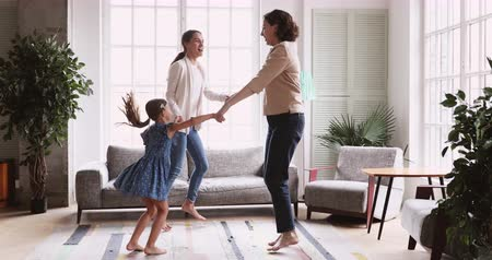 den matek : Happy friendly 3 three age generation women dancing together in living room. Active multigenerational female family having fun. Old grandma, young adult mom daughter and small granddaughter play at home Dostupné videozáznamy