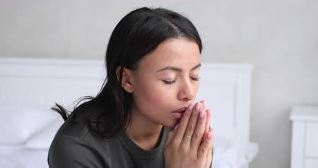 söylemek : African christian young woman praying with hope eyes closed sit on bed in morning, spiritual religious mixed race lady say prayer praise thank in worship holding hands clasped together, close up view Stok Video