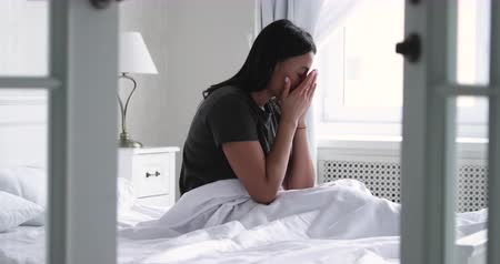 pesadelo : Depressed young african american woman sit in bed wake up feel stress anxiety after bad sleep nightmare dream concept sit alone in bedroom, worried mixed-race lady suffer from insomnia in the morning Stock Footage