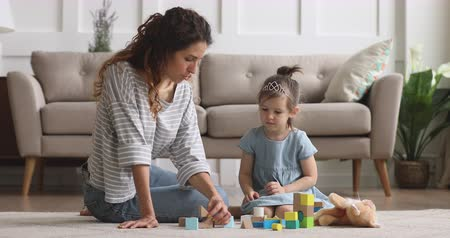 costruire : Adorable small kid girl wearing crown sitting on floor carpet with young nanny babysitter, playing with colorful wooden cubes. Happy mother enjoying free leisure time with little preschool daughter.