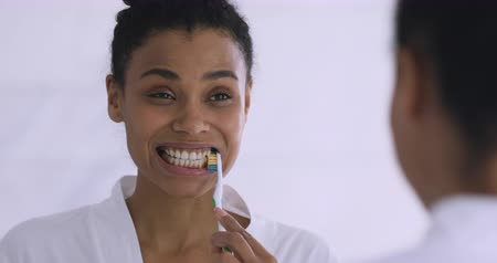 yenirce : Smiling young african ethnicity woman in bathrobe using toothbrush, cleaning mouth with toothpaste. Happy healthy biracial girl doing morning routine dental care, looking in mirror at bathroom. Stok Video