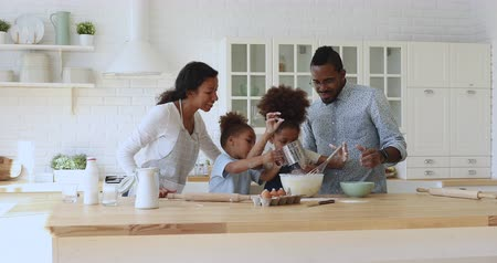 fırçalamak : Happy african ethnicity young couple parents watching kids siblings mixing eggs with flour, using whisk at modern kitchen. Joyful full family having fun, enjoying cooking process on weekend at home. Stok Video