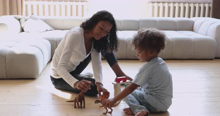 etnia africano : Happy young african american mother nanny babysitter holding toys dinosaurs cubes, playing with little cute preschool biracial kid boy on warm heated wooden floor in modern living room at home.