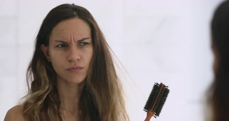 klaar : Head shot close up stressed millennial mixed race woman looking at mirror, brushing hair. Irritated annoyed young girl dissatisfied with damaged dry hair condition, hard to style, morning routine. Stockvideo