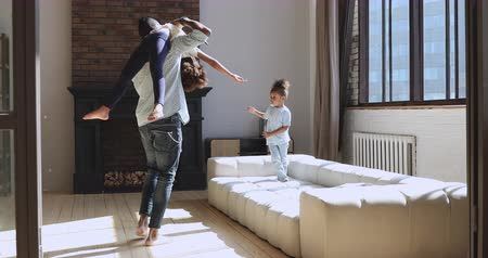 brother sister barefoot : Carefree young african american father dancing barefoot on heated wooden floor with cute daughter on shoulder. Happy biracial man having fun with small adorable children, playing together at home.